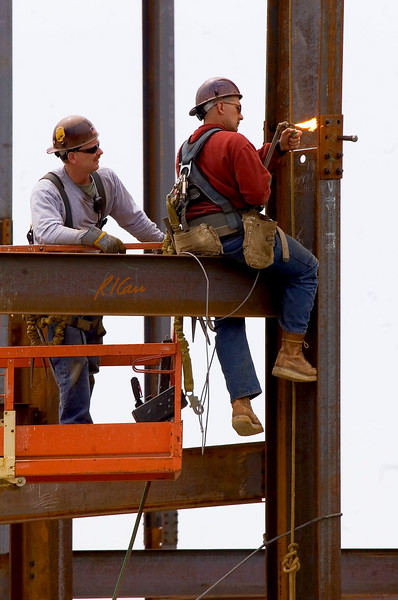 Structural ironworker lights acetylene torch from common butane lighter to enlarge bolt hole so upper column section can be bolted to splice plate. Torch is fed acetylene and oxygen through hoses from acetylene and oxygen compressed gas tanks. Ashley Terrace, Ann Arbor, Michigan April, 2007.