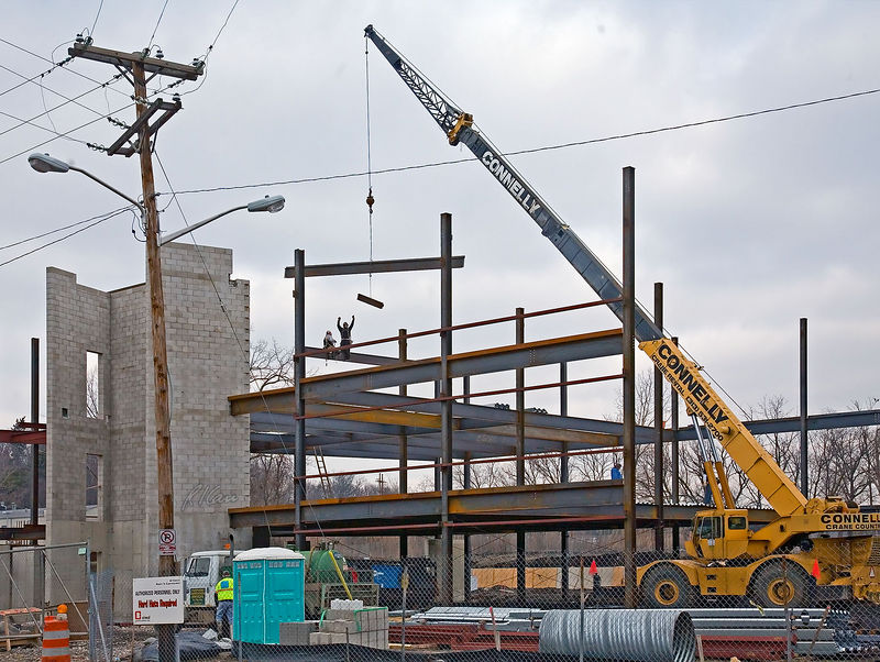 Steel construction/erection: Grove wheel mounted self-propelled hydraulic telescoping boom mobile crane lifts two wide flange structural steel sections to be placed by two ironworkers. The lower steel section is ~8 ft long is to be erected first and the upper is ~30 ft long second. The ironworkers are in position, each with a foot to either side of  an erected wide flange section, one standing with arms raised to signal the crane operator and to grab and guide the lower section into position. Note the wires carrying electricity, on right side of site far below the end of boom. Any contact between crane boom and a high voltage wire such as here, creates an extreme hazard that kills many ironworkers annually. Depot Street, February 2006.