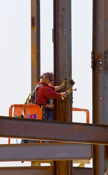 As crane cable supports structural steel wide flange column section, structural ironworker inserts tapered end of spud wrench into bolt holes in lower end of suspended column sectiona and splice plate bolted to top of previously erected column section to hold, support the column section in position to splice it to top of column below. Ashley Terrace, Ann Arbor, Michigan April, 2007.