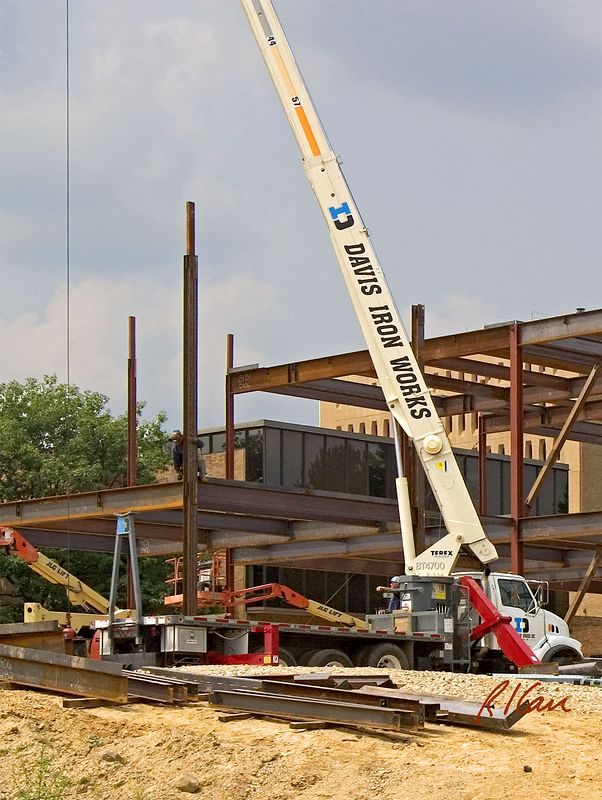 Structural steel construction: Terex BT4700 telescopic boom truck mounted crane erecting structural steel. Outriggers (red) are extended to provide stability. Biomedical Engineering, North Campus, University of Michigan, Ann Arbor, 2004.