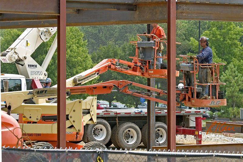 Structural steel construction: Two structural ironworker erectors wait to receive next structural steel beam to erect. Workers are supported by JLG electric boom lifts that are controlled from worker platform. Terex truck mounted erection crane is in background, and we can see its truck bed and its driver side rear outrigger (red) extended to stabilize its base while lifting steel. Biomedical Engineering, North Campus, University of Michigan, Ann Arbor, 2004.