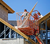Roof construction, aerial man lift: JLG 60H 60 platform height, 1,000 lb hydraulic telescoping boom aerial lift lifts two workers and plywood sheathing to roof of 4-story concrete block wall multi-unit residential building. The right-side worker is outside lift standing on roof sheathing, wearing body harness that is not connected to provide fall protection. Therefore, the only fall protection is the physical presence of the lift platform and guardrails. Roof framing is galvanized sheet metal trusses that supports plywood sheathing. Ft. Myer Beach, Florida November 2005.