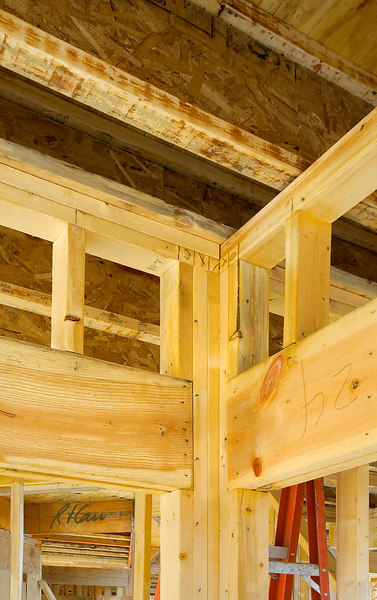 "Rough wood framing for door: Rough frame around door supports downward forces from floor/roof above. A double 2""x12"" header supports short cripple studs that support double top plates that support floor joist(s) and the loads the joist(s) carry. Joists are engineered oriented strand board/wood I joists, consisting of 2""x4"" top and bottom flanges, grooved and glued in center to an OSB (oriented strand board) vertical web. The doubled 2""x12"" wood header/lintel is supported directly on the two studs on each side of the door. Multiple studs beside the opening replace the studs that would be in the wall if there were no opening. Pencil marks on the lower top plate indicate position of cripple studs (an ""O"" at edge and vertical line in mid-opening) and full height stud (""X""), and the number ""24"" on the header indicates it is to be erected at door 24 on the rough frame erection drawing.  Ann Arbor, Michigan, October, 2006."