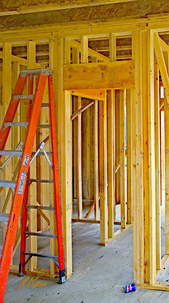 """Rough wood framing for door: Rough frame around door supports downward forces from floor/roof above. A double 2""""x12"""" header supports short cripple studs that support double top plates that support floor joist(s) and the loads the joist(s) carry. Joists are engineered oriented strand board/wood I joists, consisting of 2""""x4"""" top and bottom flanges, grooved and glued in center to an OSB (oriented strand board) vertical web. The doubled 2""""x12"""" wood header/lintel is supported directly on the two studs on each side of the door. Multiple studs beside the opening replace the studs that would be in the wall if there were no opening. Ann Arbor, Michigan, October, 2006."""