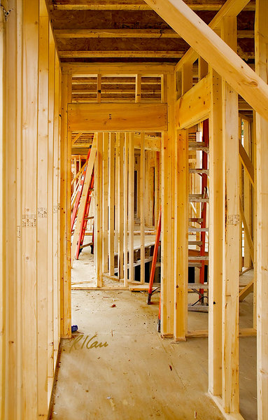"""Rough wood framing for door: Rough frame around door supports downward forces from floor/roof above. In addition, a small gap between rough frame and finished door frame prevents any deflection/warping of rough frame from deflecting/warping finished door frame and binding door. A double 2""""x12"""" header supports short cripple studs that support double top plates that support floor joist(s) and loads the joist(s) carry. The joists above bear on the double top plate, which is supported by cripple studs supported by a doubled wood header/lintel, here 2 – 2""""x12"""" set on edge side by side and supported directly on one of the two studs on each side of the door. Multiple studs beside the opening replace the studs that would be in the wall if there were no opening. Ann Arbor, Michigan, October, 2006."""