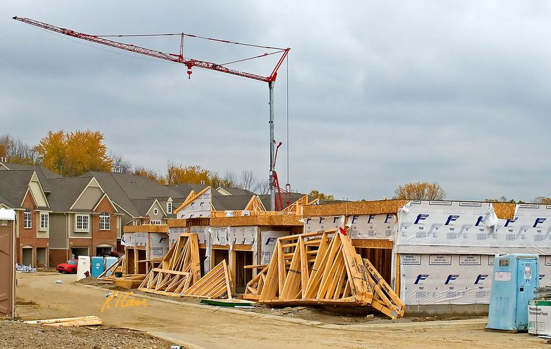 Wood frame construction, crane: First story of set of attached (common walled) residential units has been framed with dimension lumber. Prefabricated wood trusses ate stacked in front of the units, bundled together with steel straps as delivered from factory by truck. Potain HD40A self-erecting tower crane in background will place the trusses up on the onto 2nd floor. HD40A is portable, can unfold itself in less than a minute, can carry 8,800 lb maximum or 2200 lb at its largest reach of 115 ft. Residences shown were erected simularly. The white sheet covering on the sheathed framing provides resistance to wind penetration without constraining moisture from traveling from inside to outside of building. Also evident in photo are several portable chemical toilets for worker use. Ann Arbor, Michigan 2004