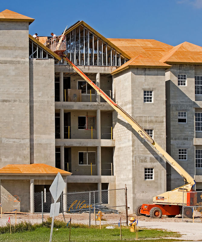 Roof construction, aerial man lift: JLG 60H 60 platform height, 1,000 lb hydraulic telescoping boom aerial lift lifts two workers and plywood sheathing to roof of 4-story concrete block wall multi-unit residential building. The left-side worker is outside lift standing on roof sheathing, wearing body harness that is not connected to provide fall protection. Therefore, the only fall protection is the physical presence of the lift platform and guardrails. Roof framing is galvanized sheet metal trusses that supports plywood sheathing. Ft. Myer Beach, Florida November 2005.