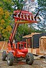 Wood frame construction: SkyTrak 8042 4-wheel drive rough terrain 42 ft hydraulic telescoping boom 8,000 lb capacity fork lift holds contractors ladders high at end of day to avoid job site thievery. Arlington Street, Ann Arbor, Michigan, 2005.