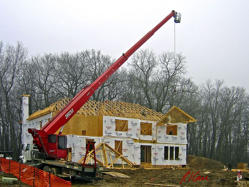 Construction crane: Manitowac 2892SX boom truck lifts truss for wood frame residence. Hydraulic crane has 100 ft telescoping boom and 28.8 ton capacity. Boom truck has outriggers out to provide stability. Ann Arbor, 2004.