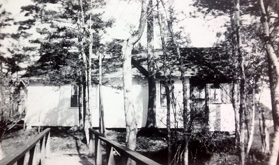 Cabin #102 with wooden bridge in foreground, 1946
