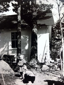 Finishing touches on cabin #103, cousins Rae and John Foster in foreground,  spring 1947