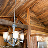 I wish I'd gotten a better shot of this, it's(to me at least) one of the most interesting details in the house. It's the intersection of the 6/12 kitchen.dining ceiling with the 10/12 vault over the great room. The 4x10 bastard  valley is supported on a 6x12 beam at the bottom and carried with lag bolts off a 4x12 shop-built truss at the upper end. There's a 2' difference in wall heights so we couldn't simply run the valley to the back wall and we really didn't want a long interior wall to support it that would interfere with the flow at the floor level. So we stuck a 6x12 on top of the wall and landed the valley on that. It really opens up both rooms.