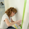 41 Oakland Street in Fitchburg, a new home being constructed by the efforts of Habitat for Humanity. Riana Szymkiewicz, of Aubuchon Hardware, tapes a wall in preparation for paint, which was donated by Aubuchon Hardware and Benjamin Moore. SENTINEL & ENTERPRISE / Ashley Green