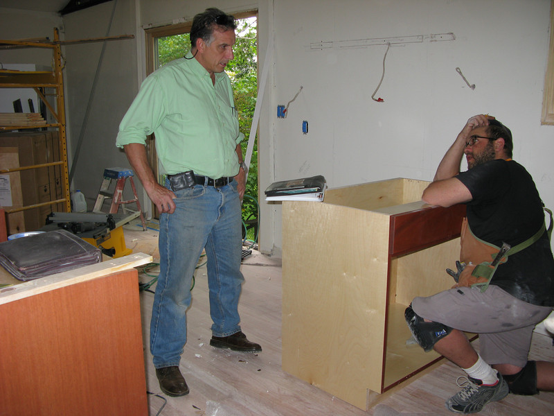 Contractor and foreman discussing schedule details.