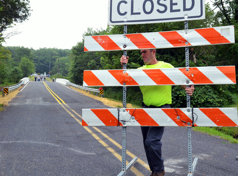 Public Works Director Jeff School moves a barrier aside, allowing traffic onto the new North Rockhill Road bridge in East Rockhill Township.   Friday, August 1, 2014.   Photo by Geoff Patton