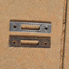 Antique strike plates from Seney entrance doors, illustrating the difference refurbishment makes.