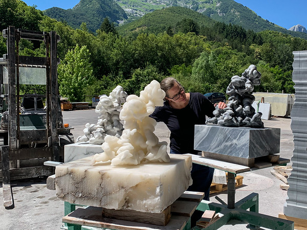 Artist working on marble and alabaster sculptures of clouds