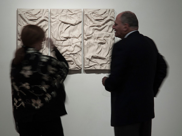 Art lovers looking at Karen LaMonte's ceramic abstract sculpture of drapery, three bas-relief panels.