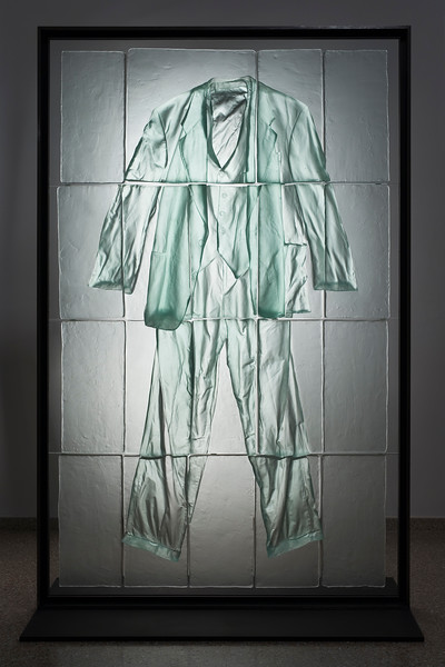 An unusual sculpture by Karen LaMonte, who usually works with female clothing, of a suit in cast glass.