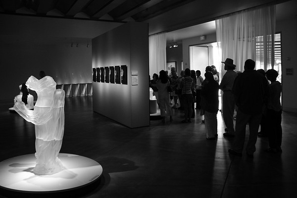 Crowds at sculpture exhibition of dresses and mirrors, which investigate cultural perceptions of beauty and body