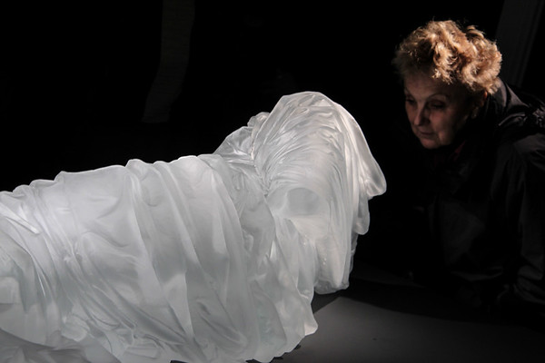 Art fan looking inside glass dress sculpture at impression of absent body during exhibition at French museum