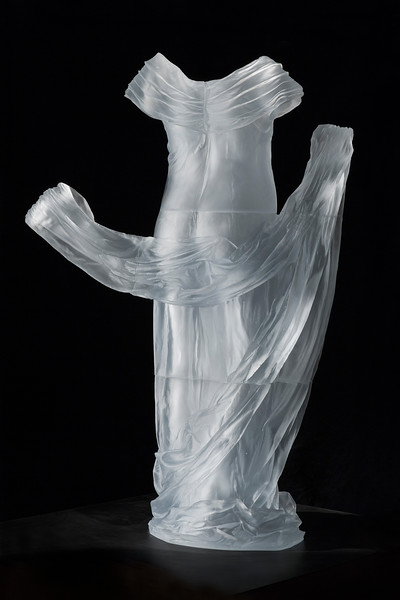 Contemporary sculpture of a life-size dress with the impression of an absent body visible through cast glass