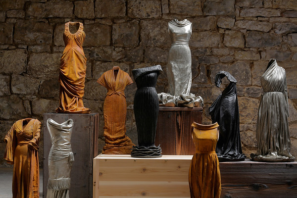 Installation of contemporary figurative sculptures of dresses by artist Karen LaMonte, bronze and rusted iron, ⅓ scale