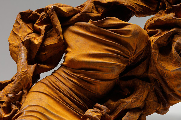 Sculpture subverting the odalisque using exaggerated drapery in rusted iron by feminist artist Karen LaMonte