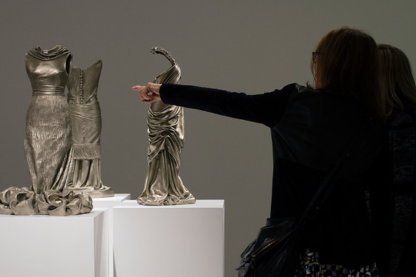 Excited art lover pointing at sculptures of dresses during exhibition of figurative artist Karen LaMonte