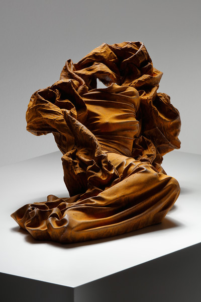 Reclining dress sculpture subverting the odalisque by feminist artist Karen LaMonte in rusted iron