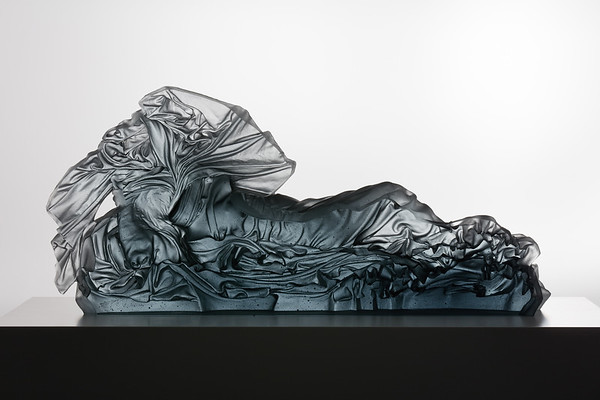 Looking through the polished back of a contemporary sculpture of a reclining figure in glass