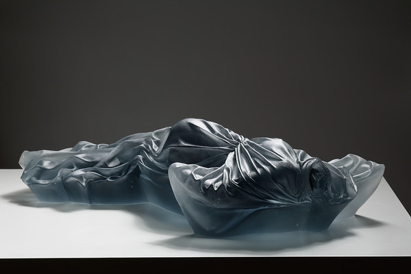Female body wrapped in drapery with elements of couture and fashion, ancient and modern, in a cast glass culpture by Karen LaMonte