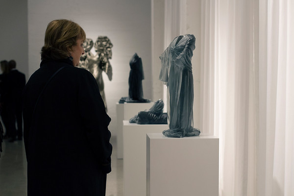 Viewers at art exhibition with sculptures of dresses and wrapped female forms by Karen LaMonte