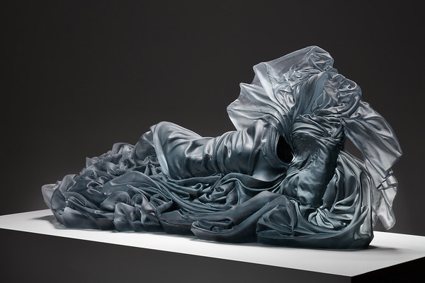 Baroque drapery on contemporary sculpture of a reclining figure, cast glass