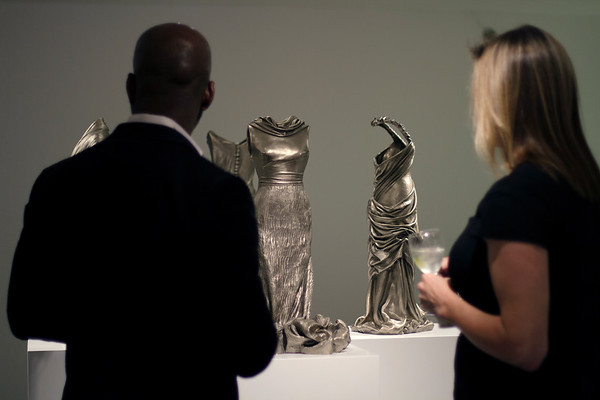 Art lovers at exhibition of contemporary art with sculptures of female forms wrapped in dresses