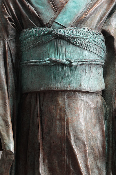 "Detail of artwork of kimono in bronze called Young Bijin. 46"" x 19"" x 17"""