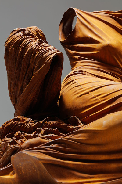 Detail of sculpture of a dress without a body rendered in rusted iron examines culture and identity