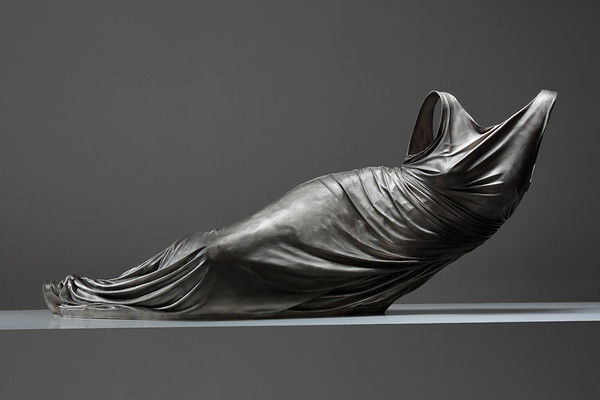 Sculpture of reclining female form shown as a dress without a body, subverts the male gaze