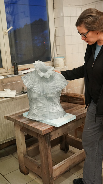 Artist in studio with raw glass casting of top of dress