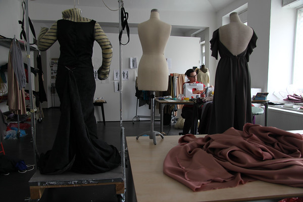 Artist working in studio sewing dresses for Nocturne and Etude sculptures.  Fashion dress mannequins in the foreground.