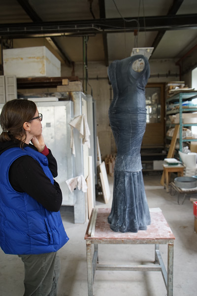 Artist at foundry working on cast glass sculpture of dress without a body