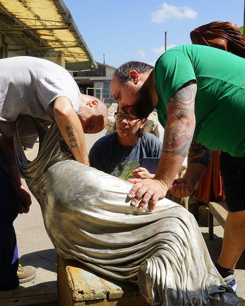Artist and team from metal foundry working on white bronze Nocturne sculpture of reclining dress