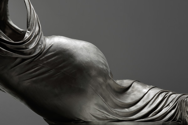 Detail of white bronze sculpture of a reclining female form shown as a dress without a body, subverts the tradition of the odalisque
