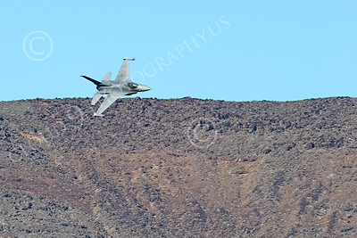 MLLF 00007 A Lockheed Martin F-16 Fighting Falcon USAF jet fighter, ED code, flies low over a ridge line into a canyon on a training mission, military airplane picture by Peter J Mancus