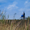 Description - Biker on Levee <b>Title - Waiting on the Ridge</b> <i>- Adrienne Bergen</i>