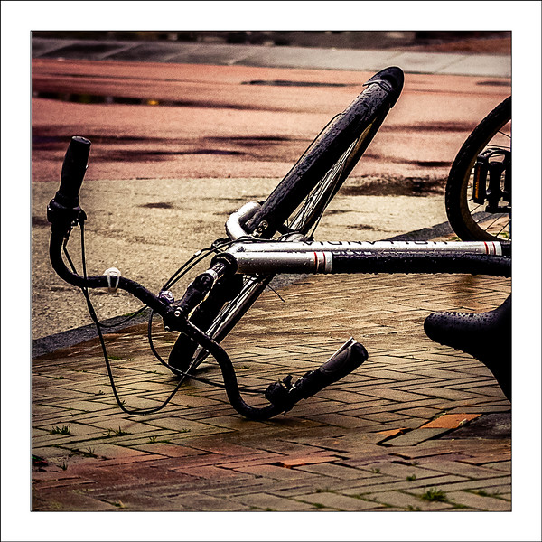 Day 12 Fallen but not beaten  It's getting boring but we had another windy and wet day. This is not my bike, I did find mine in similar shape a few hours later though. It was a fast placeholder just in case I would not have time to shoot people waiting at the busstop next to the building I would be spending the afternoon. There was no time indeed and at five it was already dark so all I had was this one and a few failed eveningshots of horizontally blown banners.
