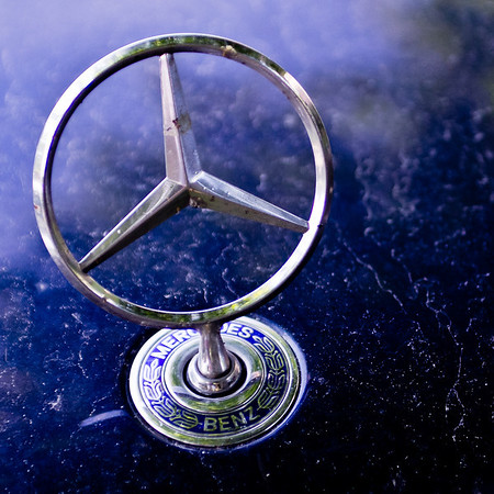 04 - Mercedes  My dad's favorite brand in cars, he owned some during the years he was on the road a lot. They are sturdy and reliable. One saved my mom & me in a carcrash once. The front was wrinkled up to the window. We were unharmed and probably would not have survived in a normal car.  Dad was definitely with me today once I had decided to look for the real star. When driving to work I saw a beige one parked in the next street and I decided to shoot it on my way back. I wanted a darker background, hopefully blue. Next road a silver one drove behind me and I saw 4 more coming towards me. So I started thanking my dad for his signs. On my way back I decided to start hunting parking lots in the village close to mine and the first car driving towards me was again the right kind of Mercedes. The first parking lot I stopped had 2 right cars, a beige and a blue. The one I shot was the 10th I saw today. The beige one was still parked a street away from my home but the blue one turned out just fine. Thanks dad, you were a great help!