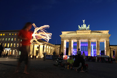 A street performer practices his act in front of the Brandenburg Gate