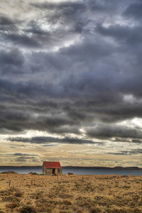A lone shack on the wind-swept steppe of Patagonia; 30 miles north of Punta Arenas, Chile along Route 9. (HDR)