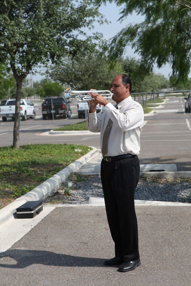 Bugler plays taps at LZRGV Healing Wall news conference.
